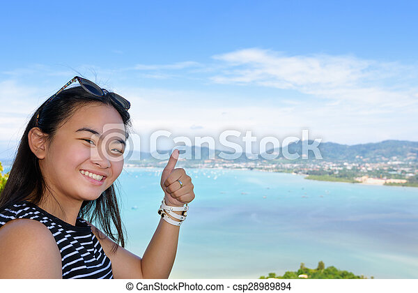 Woman tourist lifting thumb praise beautiful of sea in Phuket, Thailand - csp28989894