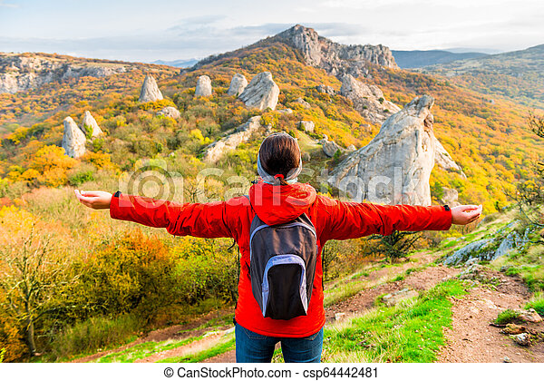 Woman Tourist with a backpack with open arms enjoying the autumn landscape in the mountains - csp64442481