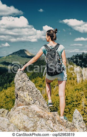 Woman Traveler with Backpack hiking in Mountains with beautiful landscape - csp52983819