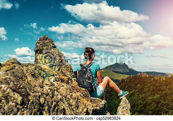 Woman Traveler with Backpack hiking in Mountains with beautiful landscape - csp52983824