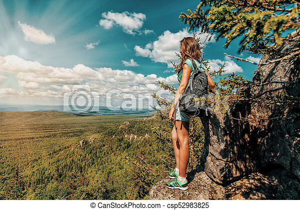 Woman Traveler with Backpack hiking in Mountains with beautiful landscape - csp52983825
