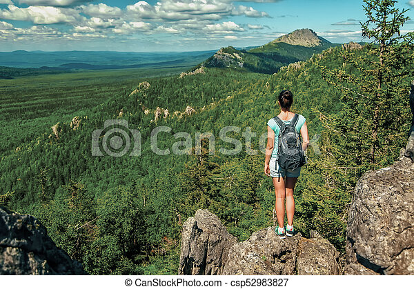 Woman Traveler with Backpack hiking in Mountains with beautiful landscape - csp52983827