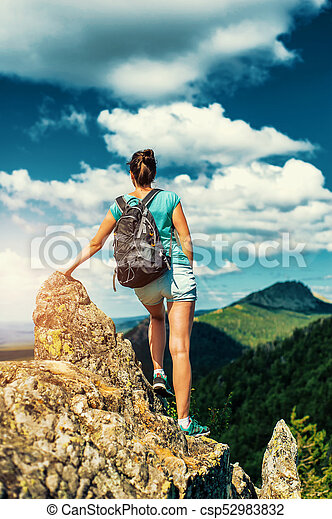 Woman Traveler with Backpack hiking in Mountains with beautiful landscape - csp52983832