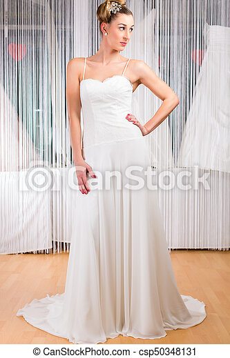 Woman Trying Wedding Dress In Shop