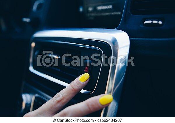 Woman turning on car emergency lights - csp62434287