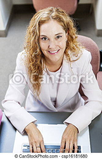 Woman typing on laptop computer in office at work - csp16181680