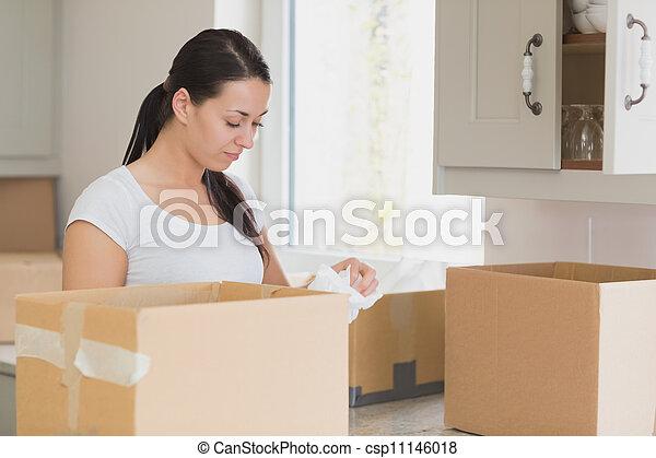Woman unpacking in kitchen - csp11146018