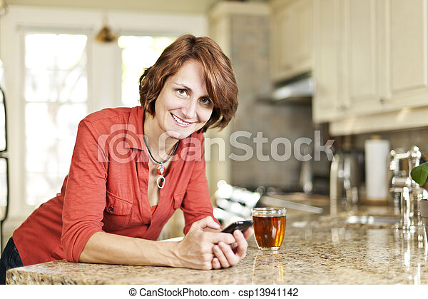Woman using cell phone at home - csp13941142