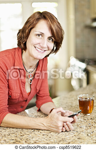 Woman using cell phone at home - csp8519622