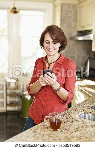 Woman using cell phone at home - csp8519593