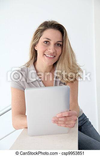 Woman using electronic tablet at home - csp9953851