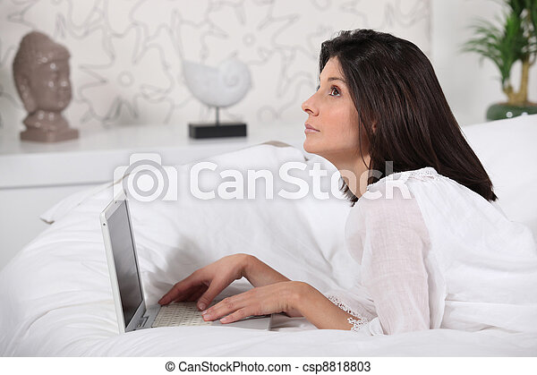 Woman using her laptop in bed - csp8818803