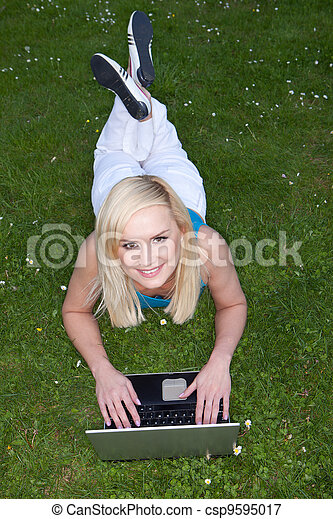 Woman using her laptop on the grass - csp9595017