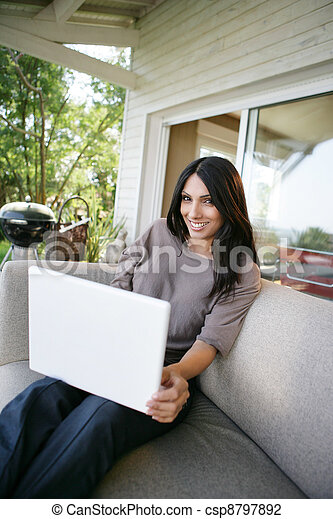 Woman using her laptop outdoors - csp8797892