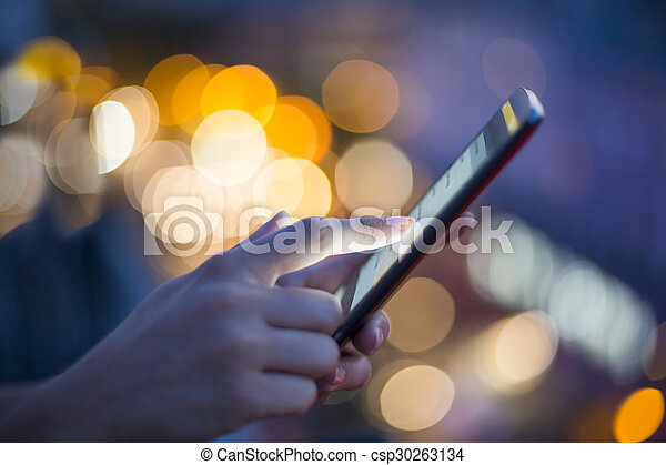 Woman using her mobile phone, city skyline night light background - csp30263134