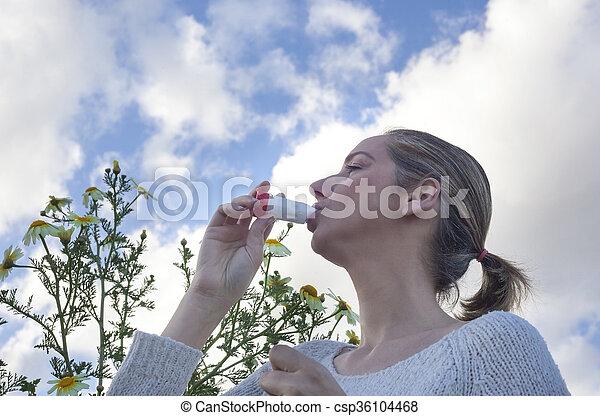 woman using inhaler to treat asthma allergic - csp36104468