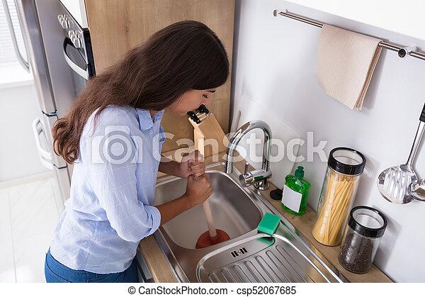 Woman Using Plunger In Blocked Kitchen Sink