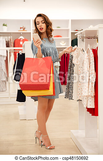 Woman using smartphone while looking through clothes - csp48150692