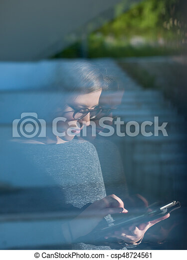 Woman using tablet at home by the window - csp48724561