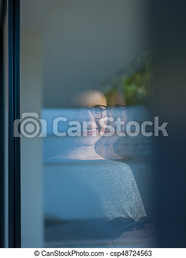 Woman using tablet at home by the window - csp48724563