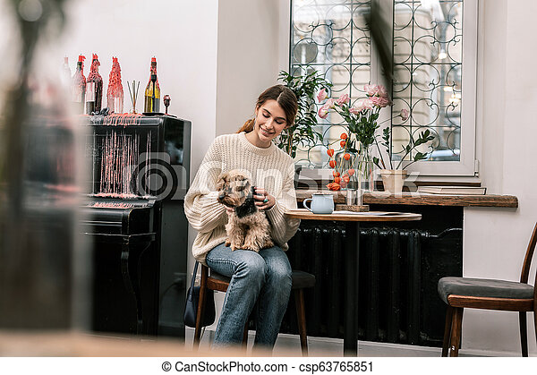 Woman visiting a dog-friendly cafe with her little friend - csp63765851