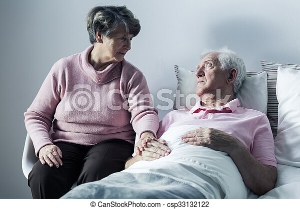 Woman visiting man at hospice - csp33132122