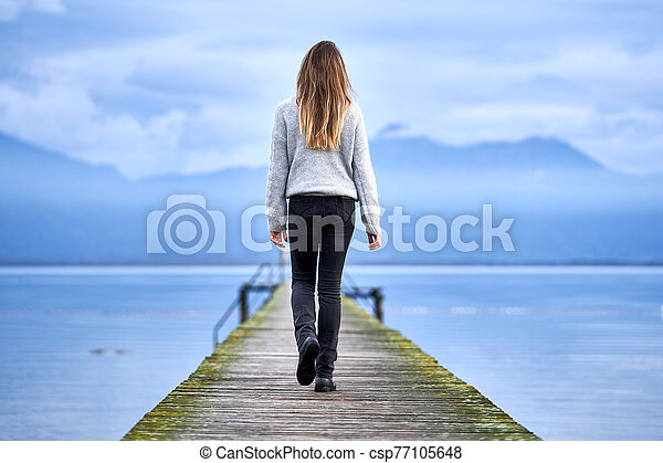 Woman walking in a jetty facing the lake - csp77105648