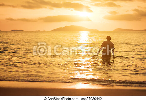Woman walking in the sea in sunset - csp37030442