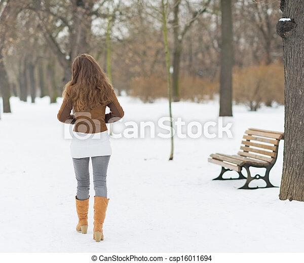 Woman walking in winter park . rear view - csp16011694