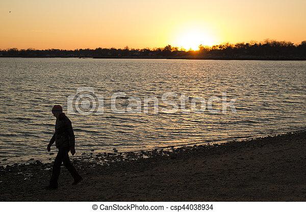 woman walking on beach at sunset - csp44038934