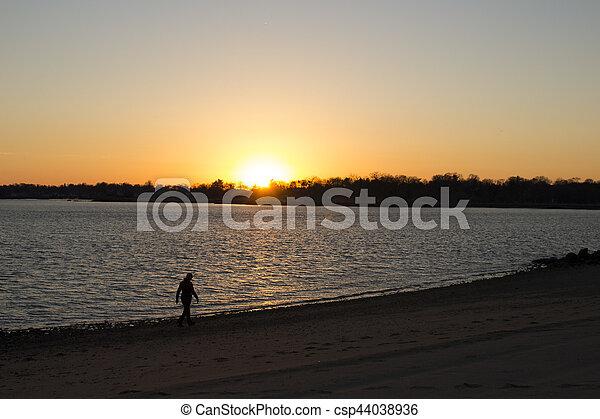 woman walking on beach at sunset - csp44038936