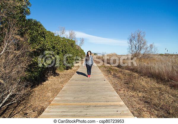 Woman walking on long wooden boardwalk trail - csp80723953