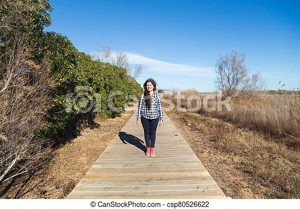 Woman walking on long wooden boardwalk trail - csp80526622