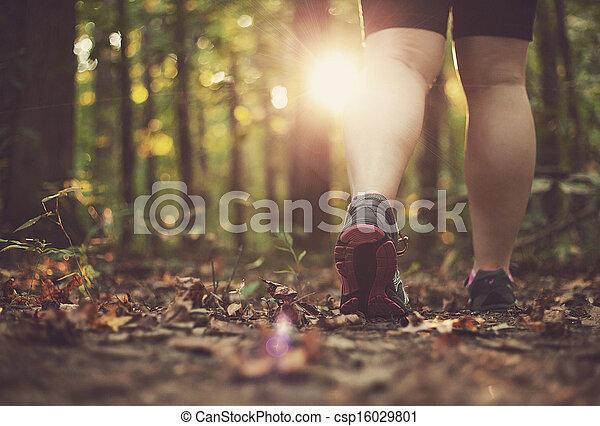 Woman walking through forest - csp16029801