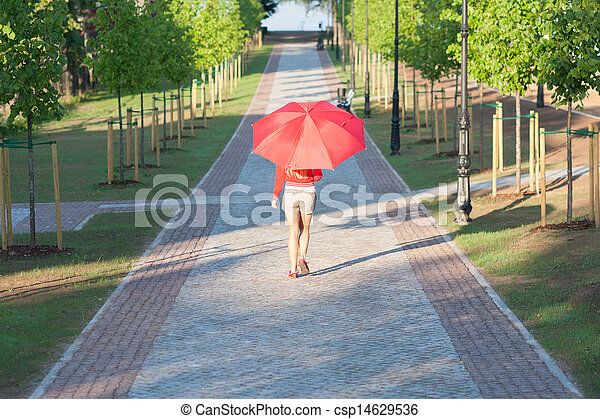 Woman walking with red umbrella on sunny morning - csp14629536