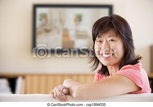 Woman watching television smiling - csp1894035