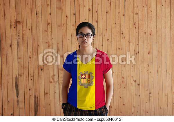 Woman wearing Andorra flag color shirt and standing with two hands in pant pockets on the wooden wall background. - csp85040612