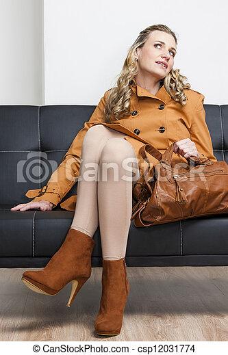woman wearing brown coat with a handbag sitting on sofa - csp12031774