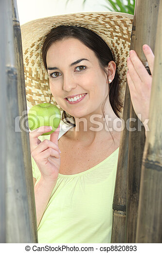 Woman wearing hat and holding green apple - csp8820893