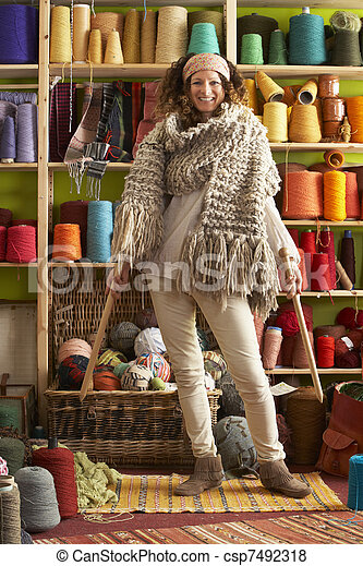 Woman Wearing Knitted Scarf Standing In Front Of Yarn Display - csp7492318