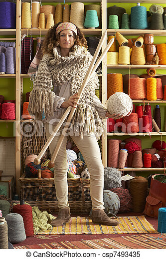 Woman Wearing Knitted Scarf Standing In Front Of Yarn Display Holding Giant Needles - csp7493435