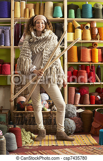 Woman Wearing Knitted Scarf Standing In Front Of Yarn Display Holding Giant Needles - csp7435780