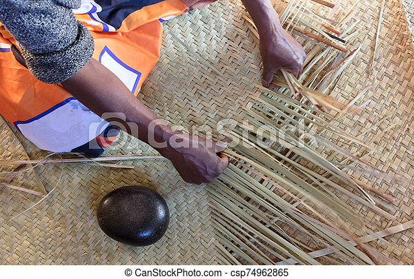 Woman weaving rug out of grass reeds - csp74962865