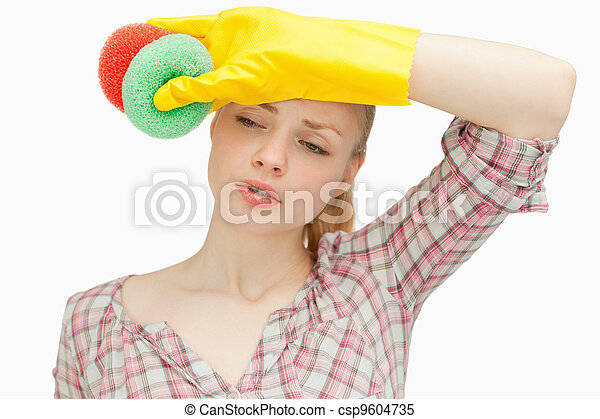 Woman wiping her forehead while holding sponges - csp9604735