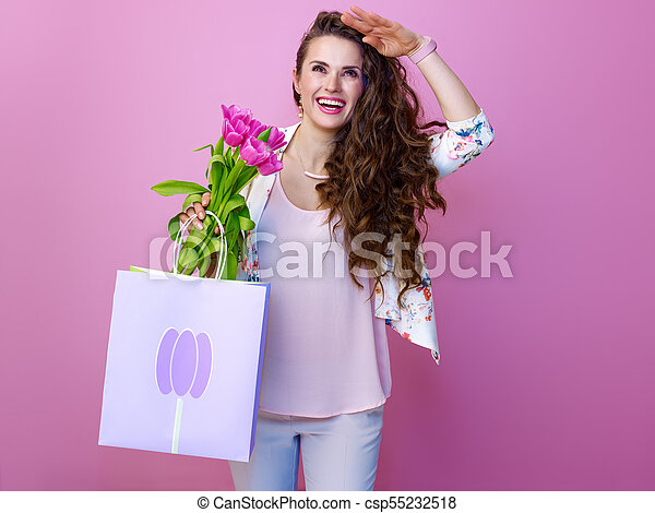 woman with a bouquet of flowers and shopping bag looking into the distance - csp55232518