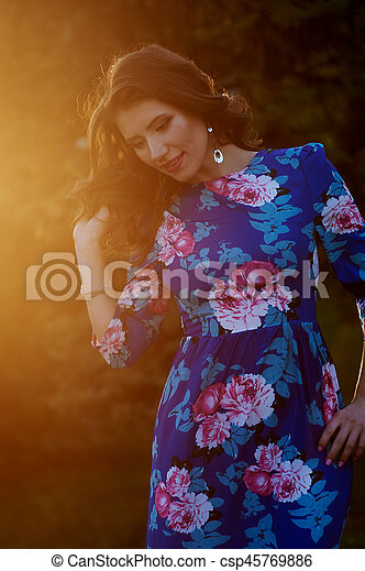 Woman with a hairdo in the sunset rays of the sun - csp45769886