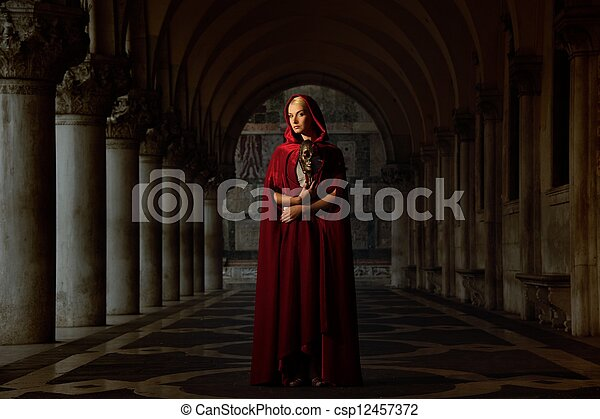 Woman with a mask wearing red cloak outdoor - csp12457372