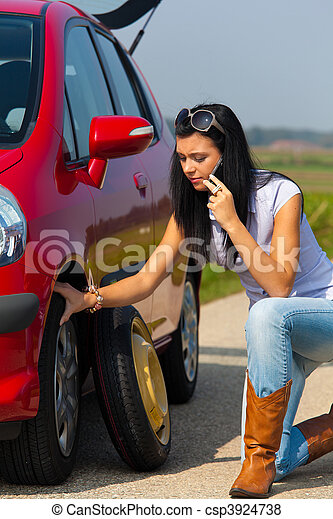 Woman with a tire in a car breakdown - csp3924738
