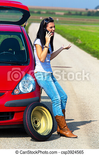 Woman with a tire in a car breakdown - csp3924565