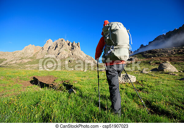 woman with backpack hiking in mountains - csp51907023